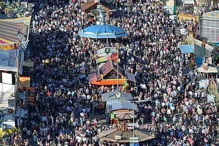 Zahlreiche Menschen gehen bei Sonnenschein über das Oktoberfest-Gelände. In der Pandemie scheint ein solches Massen-Fest kaum denkbar. Foto: picture alliance/dpa/Archivbild