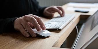 Mann klickt Maus am Computer