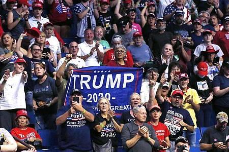 Anhänger von Präsident Donald Trump machen Stimmung. Foto: Sue Ogrocki/AP/dpa