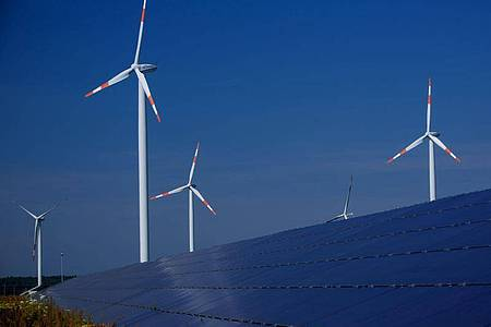 Windräder zur Stromerzeugung drehen sich in Mecklenburg-Vorpommern hinter einem Solarpark. Foto: Jens Büttner/dpa-Zentralbild/dpa