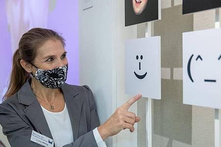 Luna Mittig erläutert Details zur Mimik und Gestik an einer Installation im Museum für Kommunikation ijn Nürnberg. Foto: Daniel Karmann/dpa