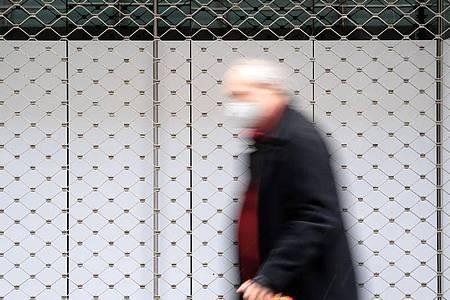 Ein Mann geht in einer Innenstadt an einem geschlossenen Geschäft vorbei. Foto: Sven Hoppe/dpa