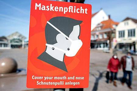 Ein Schild mit der Aufschrift «Maskenpflicht» hängt auf dem Marktplatz im niedersächsichenAurich. Foto: Hauke-Christian Dittrich/dpa