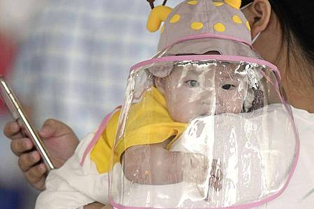 Ein Kleinkind trägt am Flughafen von Wuhan in Zentralchina einen Gesichtsschutz. Foto: -/kyodo/dpa