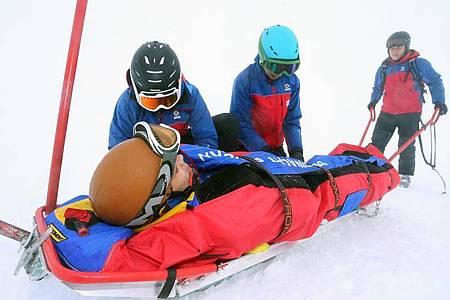 Teilnehmer eines Lehrganges für Bergretter der Bergwacht trainieren auf dem Nebelhorn bei Oberstdorf (Bayern) den Umgang mit einem Ackja. Foto: picture alliance / Karl-Josef Hildenbrand/dpa