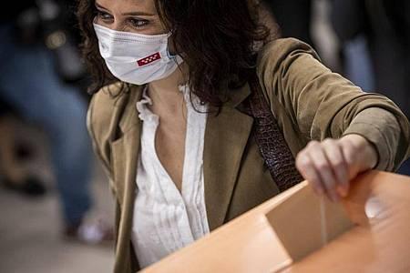 Isabel Diaz Ayuso, Präsidentin der Gemeinde Madrid und Kandidatin zur Wiederwahl, wirft ihre Stimme in eine Wahlurne. Foto: Bernat Armangue/AP/dpa