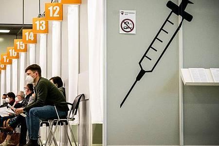 Menschen warten im Corona-Impfzentrum auf dem Messegelände Berlin auf ihre Impfung. Foto: Michael Kappeler/dpa