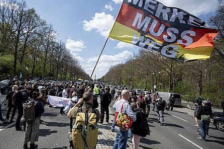 «Merkel muss weg» steht auf der Flagge eines Demonstranten beim Protest gegen die Änderung des Infektionsschutzgesetzes in Berlin am 21. April (Symbol). Foto: Fabian Sommer/dpa