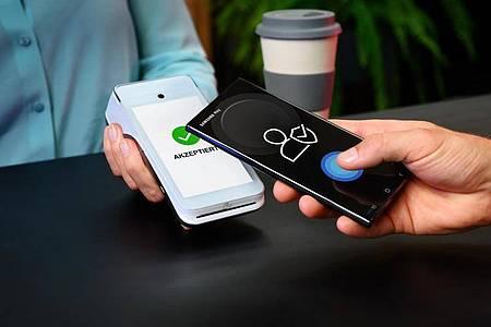Das Smartphone kurz ans Terminal halten und schon ist bezahlt. So funktioniert Samsung Pay. Foto: Samsung/dpa-tmn