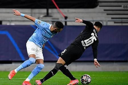 Manchester Citys Riyad Mahrez und Gladbachs Ramy Bensebaini (r) kämpfen um den Ball. Foto: Marton Monus/dpa