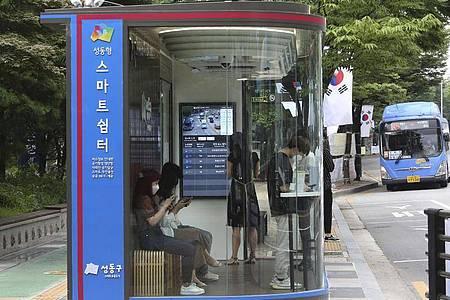 Menschen warten in Seoul in einem «smarten» Wartehäuschen auf den Bus. Foto: Ahn Young-Joon/AP/dpa