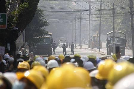 Demonstranten in Mandalay tragen gelbe Schutzhelme und beobachten auf einer blockierten Straße die Polizei. Foto: Uncredited/AP/dpa
