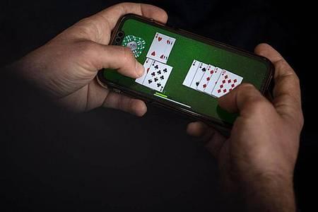 Das nächste Spiel ist auf dem Smartphone nur wenige Fingertipper entfernt und kann Abhängige schnell in Versuchung führen. Foto: Sina Schuldt/dpa/dpa-tmn