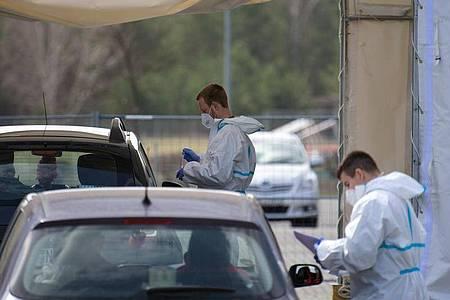 Mitarbeiter der Johanniter-Unfall-Hilfe e.V. testen in einem Zelt des «Drive in»-Corona-Test in Oranienburg die Insassen zweier Autos auf Corona. Foto: Soeren Stache/dpa