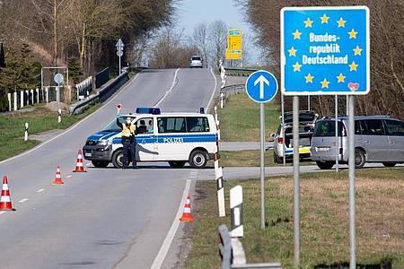 Polizisten stehen an der Bundesstraße 512 in der Nähe von Neuhaus am Inn an einer Kontrollstelle an der Grenze zu Österreich. Foto: Sven Hoppe/dpa