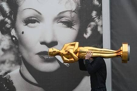 Ein Oscar vor dem Porträt von Marlene Dietrich. Foto: Ralf Hirschberger/dpa-Zentralbild/dpa