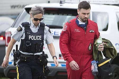 Ein Pilot geht mit einer Polizistin an der Absturzstelle vorbei. Foto: Jonathan Hayward/The Canadian Press/AP/dpa