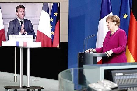 Bundeskanzlerin Merkel und Emmanuel Macron bei einer Pressekonferenz. Frankreichs Präsident ist per Video zugeschaltet. Foto: Kay Nietfeld/dpa-Pool/dpa