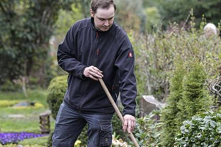 Nico Hemsteg pflegt auf einem Friedhof in Duisburg ein Grab. Foto: Kirsten Neumann/dpa-tmn