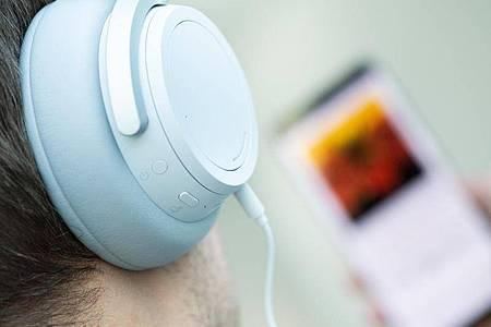 Ein junger Mann hört mit Kopfhörern Musik von seinem Smartphone. Foto: Franziska Gabbert/dpa-tmn/dpa