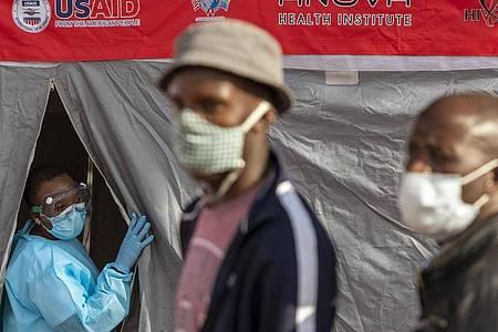 Menschen stehen in Johannesburg vor einem Zelt an, um sich auf eine Infektion mit dem Coronavirus testen zu lassen. Foto: Themba Hadebe/AP/dpa