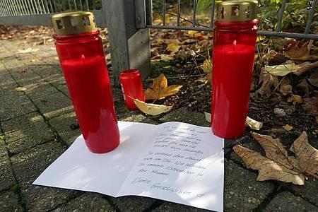 Kerzen und ein Brief liegen vor dem Gelände in Duisburg, auf dem ein Mädchen tot aufgefunden wurde. Foto: David Young/dpa