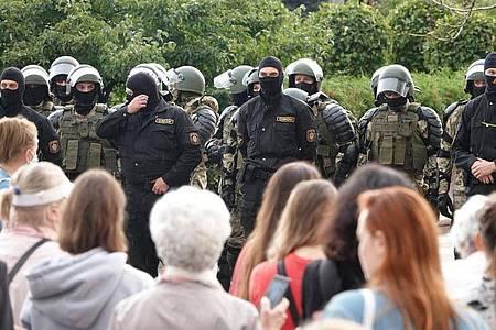 Demonstranten und Einsatzkräfte der Sonderpolizei OMON stehen sich am Unabhängigkeitsplatz in Minsk gegenüber. Foto: Ulf Mauder/dpa