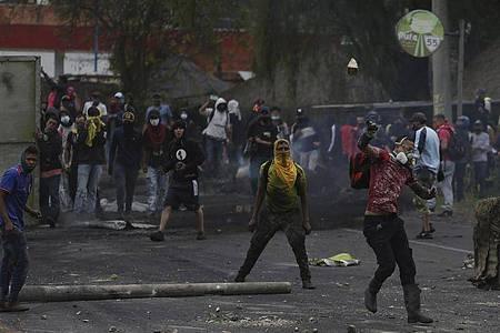 Vermummte Anti-Regierungs-Demonstranten werfen in Gachancipa Steine auf die Sicherheitskräfte während anhaltender Proteste. Foto: Ivan Valencia/AP/dpa