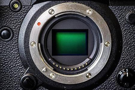 Was da grün schimmert, ist der Kamera-Sensor. Er ist bei Systemkameras um ein Vielfaches größer als bei Smartphones. Foto: Sina Schuldt/dpa-tmn