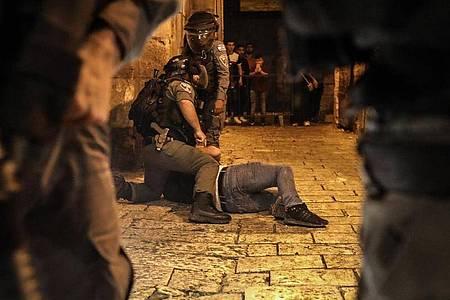 Israelische Sicherheitskräfte nehmen bei Zusammenstößen in der Altstadt von Jerusalem einen Mann fest. Foto: Ilia Yefimovich/dpa