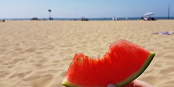 Ein angebissenes Stück Wassermelone mit Strand im Hintergrund