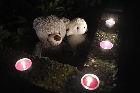 Teddybären und Kerzen liegen vor dem Haus, in dem die toten Kinder gefunden wurden. Foto: Roberto Pfeil/dpa