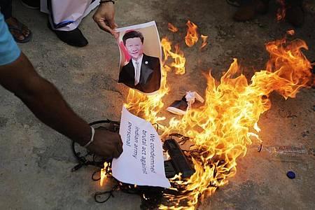 Auf einer Straße im indischen Ahmedabad wird ein Foto des chinesischen Präsidenten Xi Jinping verbrannt. Foto: Ajit Solanki/AP/dpa