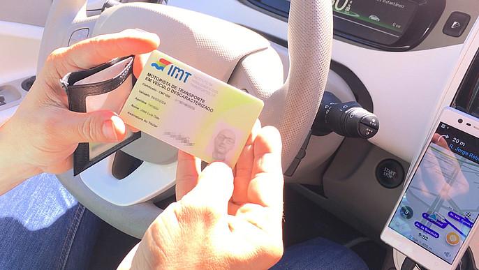 Zwei Hände halten eine Lizenz in einem Auto