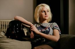 Hannah Schürkamp sitzt auf einem Sofa und schaut zur Seite