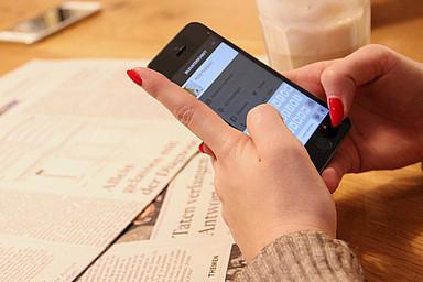Frau tippt etwas auf dem Smartphone in einer App ein