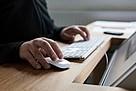 Eine Person die eine Computertastertur mit Maus bedient