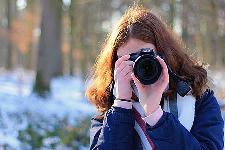 Frau fotografiert im Schnee in die Kamera