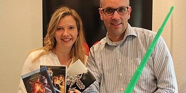 Ina Artig und Markus Bussmann mit Star Wars DVDs und grünem Lichtschwert