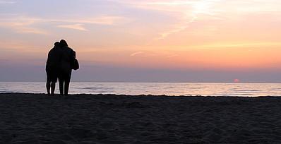Zwei Personen stehen am Meer und stützen sich gegenseitig
