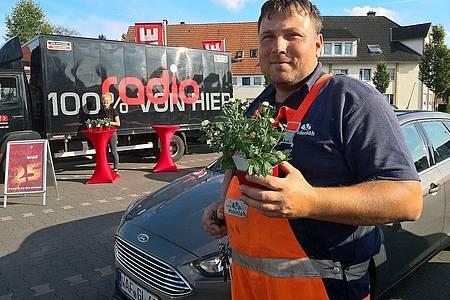 Gärtner hält Blume in der Hand, im Hintergrund sieht man den Radio WAF Verteilstand
