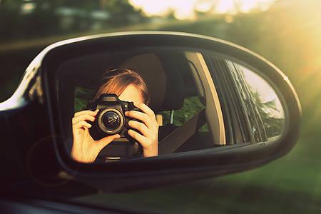 Frau fotografiert mit der Kamera in den Rückspiegel eines Autos