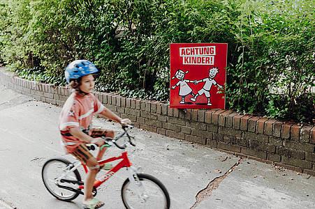 Junge mit Fahrrad neben Achtung Kinder-Plakat