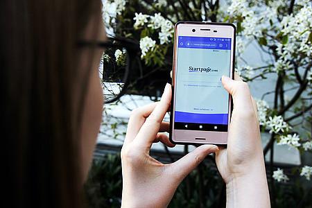 Frau hält Smartphone in den Händen auf dem Startpage geöffnet ist