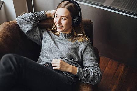 Frau liegt im Sessel und hört Radio WAF live