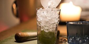 Eiswürfel werden in ein Cocktailglas geschüttet