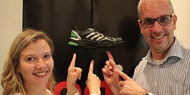 Ina Artig und Markus Bussmann halten Sneaker in die Kamera