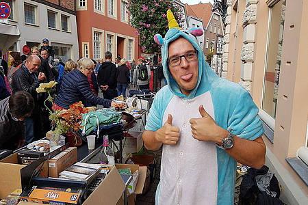 Verkäufer eines Flohmarkt-Standes hat sich als Einhorn verkleidet und zeigt Daumen hoch
