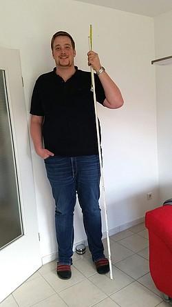 Größter Mann aus Warendorf steht mit einem Maßband an der Wand