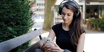 Frau sitzt auf einer Bank und streamt die WM